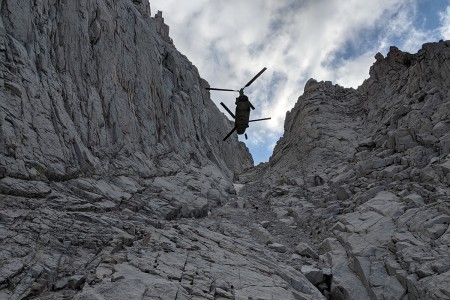 A U.S. Army CH-47F Chinook helicopter assigned to the California Army National Guard, hovers as an injured hiker is hoisted on a litter from an area 13,800 feet up Mount Whitney in Inyo County, Calif., Aug. 25, 2019. The Chinook inserted a team from Inyo County Search and Rescue who provided aid to the woman and helped with her hoist rescue into the helicopter. (Photo courtesy of Inyo County Search and Rescue)