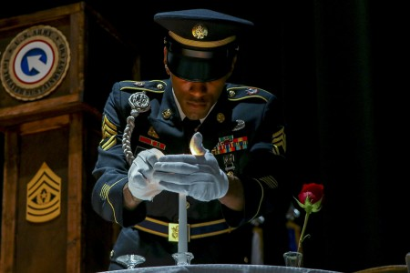 Sgt. 1st Class Anthony Bynum prepares to light a candle at the Prisoner of War/Missing in Action (POW/MIA) table during the 1st TSC noncommissioned officer (NCO) induction ceremony, Sept. 30, 2019 at the Olive Theater, Fort Knox, Ky. The table recognizes those members that are missing and honors their memory and service. (U.S. Army photo by Spc. Zoran Raduka)