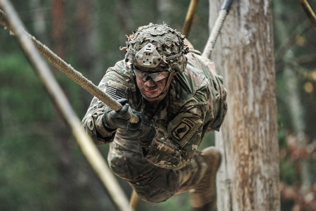 Paratroopers assigned to 91st Cavalry Regiment, 173rd Airborne Brigade, pulls himself across a rope obstacle while participating in the unit's Spur Ride in Grafenwoehr Training Area, Germany, Nov. 20, 2019. (U.S. Army photo by Sgt. Henry Villarama)