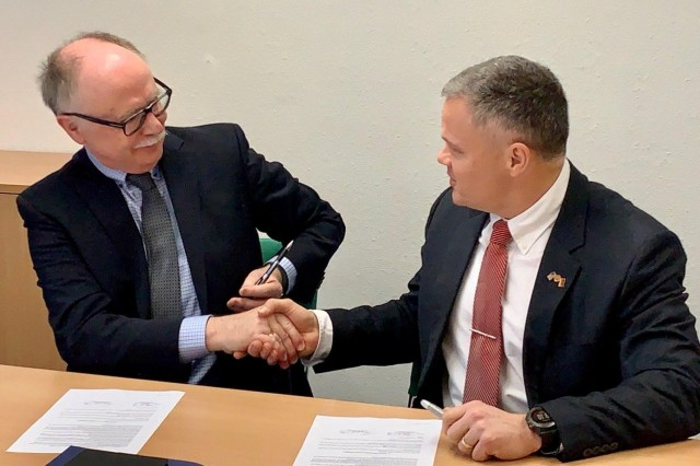 BONN, Germany -- Tommy Mize (right), director of IMCOM-Europe, and Ralf Poss, Federal Ministry of the Interior, shake hands after signing an accelerated construction measure agreement.