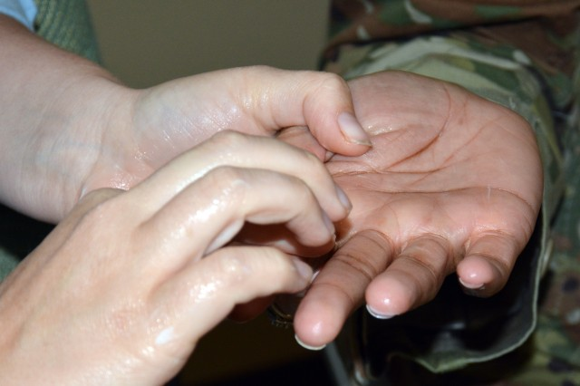 One of the interactive activities during Carl R. Darnall Army Medical Center's Centering Pregnancy program is hand massage. Centering Pregnancy is an innovative approach to prenatal care and empowers pregnant women to be healthy by taking an active role in their healthcare. Instead of having short, individual clinic appointments, participants meet in a small group setting with other women with similar due dates. Groups meet for two hours at a time, which allows for individual assessment of the baby's growth and heartbeat, as well as plenty of time for relaxed and open communication about different concerns and questions. All of the routine testing and prenatal lab work occurs in the Centering environment.