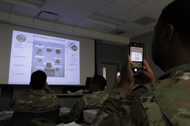 Sgt. Melvin Williams, Headquarters Support Company, 3rd Infantry Division, snaps a photo of important information Dec. 5, 2019, during the High Mobility Multipurpose Wheeled Vehicle Egress Trainer instructor, operator course, as directed to do so by James Rucker, instructor at the Virtual Training Center at Fort Stewart, Ga. The course is designed to have Soldiers become proficient on all operations of the HEAT device so they can train Soldiers on rollover safety procedures. (U.S. Army photo by Spc. Noelle E. Wiehe)
