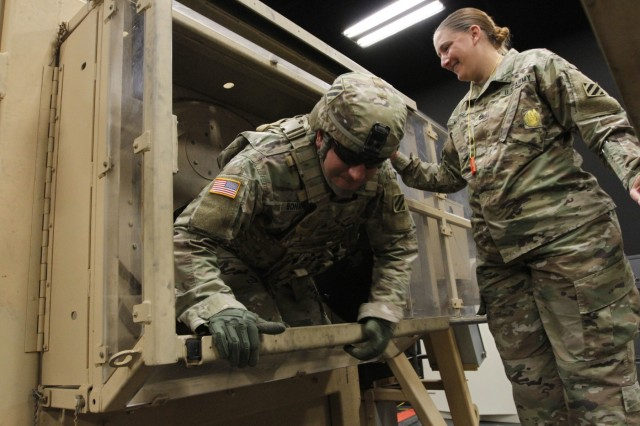 Sgt. James Bonanno, Forward Support Company, 6th Squadron, 8th Cavalry Regiment, 3rd Infantry Division, crawls from a High Mobility Multipurpose Wheeled Vehicle Egress Trainer Dec. 6, 2019, during the instructor, operator course, as Staff Sgt. Elizabeth Marose, FSC 6-8 Cav. instructs him on safety precautions at the Virtual Training Center at Fort Stewart, Ga. The course is designed to have leaders become proficient on all operations of the HEAT device. (U.S. Army photo by Spc. Noelle E. Wiehe)