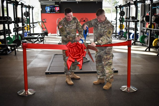 """Left, Col. Steven M. Pierce, U.S. Army Garrison Ansbach commander, and with Lt. Col. Todd Daniels, 5th Battalion, 4th Air Defense Artillery Regiment commander, cut the ribbon to open the Shipton """"We Attack"""" Fitness Center Dec. 9."""