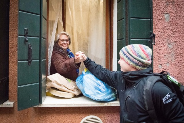 """An Italian woman shows her appreciation to BOSS Vicenza Advisor Joseph 'Rodger' Nuttall in Venice, Italy on Friday, Dec. 6, 2019. """"Seeing people come out of their homes to personally thank us for helping alleviate work on them, after they have gone through so much, was especially rewarding,"""" said Nuttall, who high-fived an older Italian woman."""