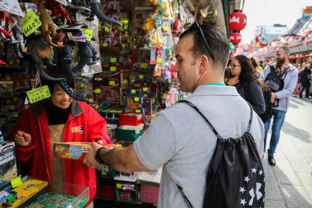 Sgt. 1st Class Gerardo Matos Negron, part of the 42nd Military Police Brigade, finishes his Christmas shopping at the Nakamise Dori street market as part of a cultural tour in Tokyo, Japan, Dec. 6, 2019.  Eighty-nine shops line the street, selling traditional souvenirs like kimonos and fans, as well as novelty items and desserts. (U.S. Army photo by Spc. John Weaver)