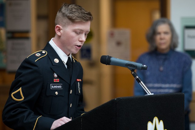 Private 1st Class Christopher Blanshard speaks about the significance of evergreen tree at a Christmas tree and Menorah lighting ceremony in the Medical Mall at Madigan Army Medical Center on Dec. 6.