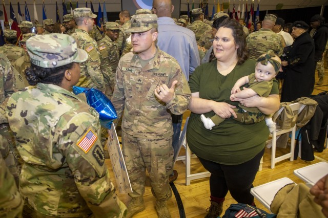 Sgt. Jeffrey Adams, 1st Theater Sustainment Command, is greeted by Soldiers alongside his family during the White Team redeployment ceremony at Sadowski Center, Dec 11th, 2019 on Fort Knox, Ky. (U.S. Army Photo by Spc. Zoran Raduka)