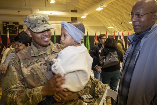 Spc. Dezmond Copeland, 1st Theater Sustainment Command, smiles at his child during his redeployment ceremony at Sadowski Center, Dec 11th, 2019 on Fort Knox, Ky. (U.S. Army Photo by Spc. Zoran Raduka)