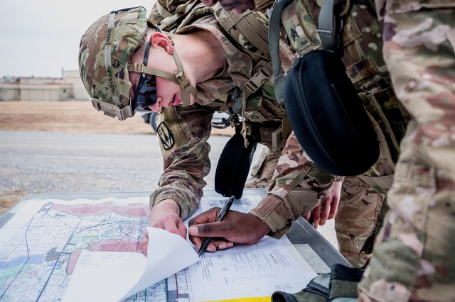 From left, Pfc. Blaise Harvilla and Sgt. Xavier Bills complete the land navigation station during the Cerberus Competition at Fort Sill, Oklahoma, Nov. 20, 2019.  Six stations were spread throughout the seven-mile route that tested competitors on military occupational specialty and basic soldiering skills.