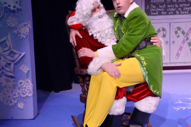 Buddy the Elf (Bryce Romleski) sits on Santa's (Keith Cash) during a recent performance of Elf Jr. The Musical at the KMC Onstage theater in Kaiserslautern. Photo by David Schwab