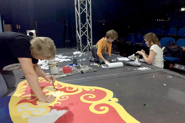 Volunteers start getting the stage ready for Elf Jr. The Musical at KMC Onstage theater in Kaiserslautern. Volunteer tech and backstage crews are just as important as actors in community theater. Photo by Beth Dougherty