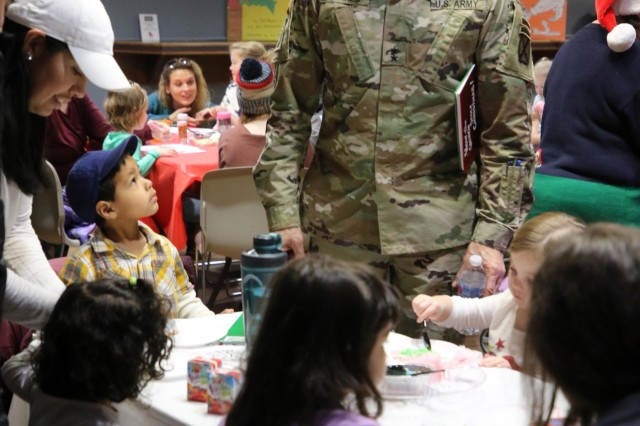 """Parents and their children were invited to the Fort Drum USO Dec. 9th for a presentation of """"How the Grinch Stole Christmas"""" by Dr. Seuss. The story was read by Maj. Gen. Brian J. Mennes as part of the United Service Organizations' ongoing Storytime Program."""