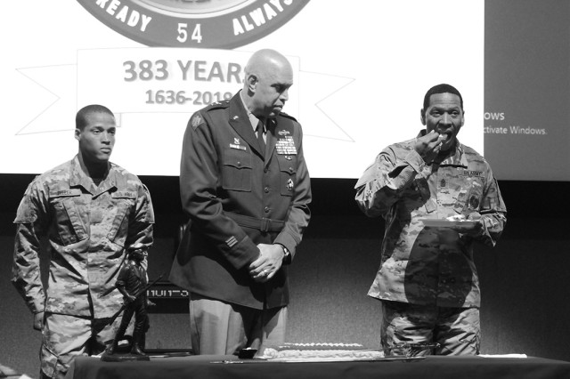 Pvt. Elias Zeller, age 17; and Maj. Gen. Michael Thompson, Adjutant General for the State of Oklahoma, watch as Sgt. Maj. Gerald James, 58, takes a bite of cake at Fort Sill's National Guard birthday celebration Dec. 13, 2019, in Snow Hall. Zeller is in week 5 of Basic Combat Training here; James is with the Fires Center of Excellence Headquarters and Headquarters Detachment.