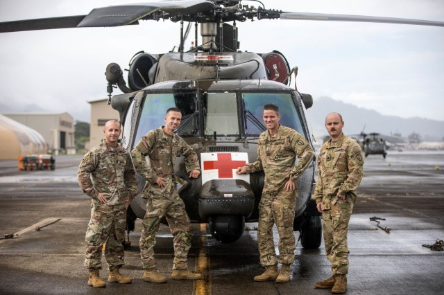 """U.S. Army MEDEVAC flight crew with Charlie Company, 3rd Battalion, 25th Aviation Regiment, General Support Aviation Battalion (GSAB), 25th Combat Aviation Brigade, 25th Infantry Division stand in front of their HH-60 Black Hawk at Wheeler Army Airfield, Hawaii from left to right is Capt. Jeremy Bowling, Sgt. Matt Standford, Chief Warrant Officer 3 Jake Beckwith, and Sgt. Zachary Hartman. The MEDEVAC flight crew is responsible for saving a life after they received a search and rescue call when a man became lost mountain biking to the summit of Mauna Kea on the island of Hawaii Oct. 10, 2019. """"We just happened to be in the right place at the right time, and I am thankful for the crew we had,"""" said Capt. Jeremy Bowling, the pilot on board. """"I was impressed by the professionalism of this crew. Everyone has to be an expert at their job. We are the only ones out there and people's lives are dependent on our hands."""" (U.S. Army photo by Sgt. Sarah D. Sangster)"""