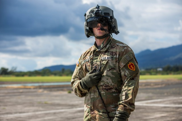 Spc. Jon Gray, a crew chief with 25th Combat Aviation Brigade, gets ready for the official review of the 25th Infantry Division's Soldiers, complete with flyover from 25th CAB helicopters Oct. 31, 2019 at Schofield Barracks, Hawaii. Soldiers wear the 25th Infantry Divisions colored patch during Tropic Lightning Week which is the first time it is displayed with the OCP uniform. (U.S. Army Photo by Sgt. Sarah D. Sangster)