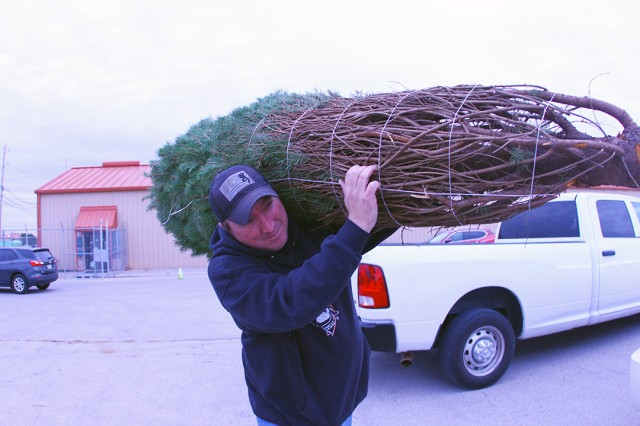 Recycle Center volunteer Phillip Smith highports a Christmas tree to a family's car Dec. 14, 2019.