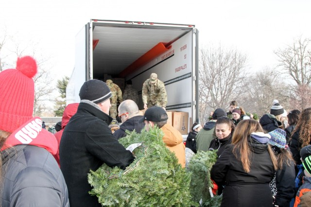 Hundreds of local civilian community members make their way to the Wreaths Across America trucks to unload and place wreaths upon graves Saturday at the West Point Cemetery.