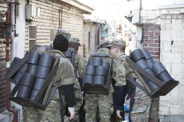 Soldiers assigned to 2nd Infantry Division/ROK-U.S. Combined Division, wait in line to deliver charcoal to local homes for the charcoal briquette distribution, Dec. 5, 2019, Dongducheon, Republic of Korea. A total of 5,000 briquettes were delivered to families during the event. (U.S. Army photo by Sgt. Yesenia Barajas)