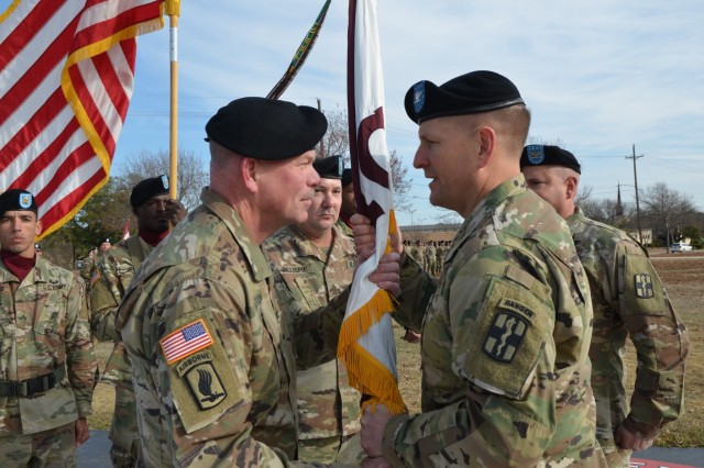 """Incoming 9th Hospital Center Commander, Col. David Hamilton, receives the unit colors from 1st Medical Brigade Commander, Col. Robert F. Howe, signaling the transfer of command during the change-of-command ceremony Dec. 12.  """"The Longhorns"""" of the 9th Hospital Center welcomed new commander, Col. David Hamilton, who served as the Deputy Commanding Officer of Womack Army Medical Center, Fort Bragg, North Carolina, before assuming command. (U.S. Army photos by Spc. Yaeri Green)"""