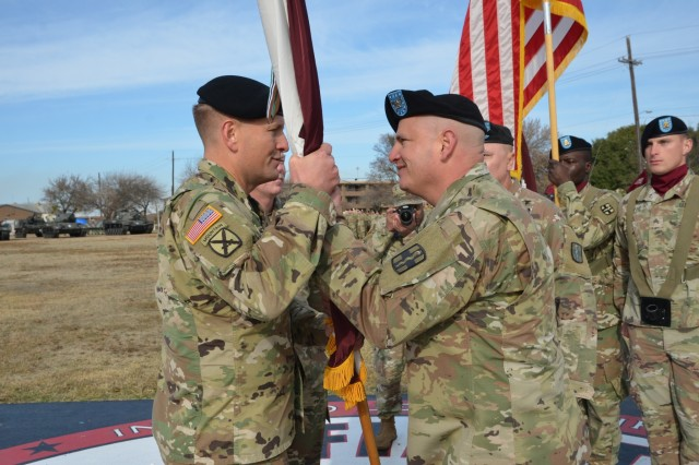 Outgoing 9th Hospital Center Commander, Col. Jeffrey S.Yarvis, passes the unit colors to 1st Medical Brigade Commander, Col. Robert F. Howe, during the change-of-command ceremony Dec. 12.  Yarvis served as the last commander of 21st Combat Support Hospital before it became the 9th Hospital Center, and now moves over to the Carl R. Darnell Army Medical Center. (U.S. Army photo by Spc. Yaeri Green)