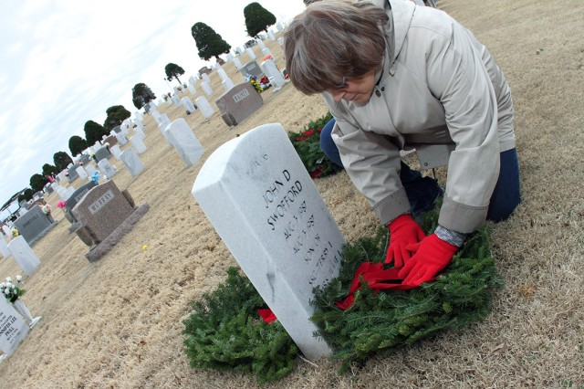 Julie Swofford gingerly places wreaths at the headstone of her husband, and son Dec. 14, 2019, at the Fort Sill Post Cemetery during the Wreaths Across America ceremony. The plot contains Sgt. 1st Class Terry Swofford, and John Swofford.