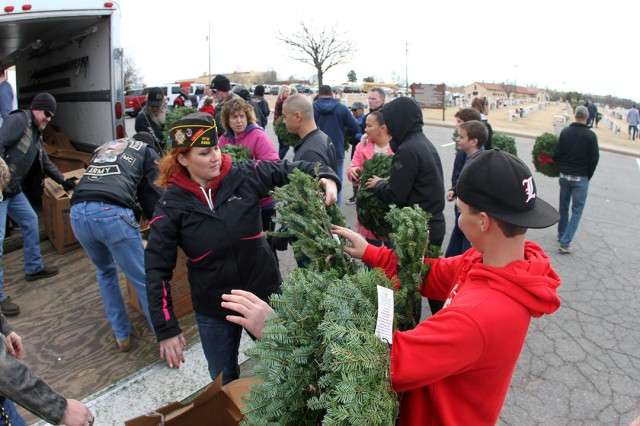 Erica Wilson-Traxler (center), VFW Post 5263 commander, passes out wreaths Dec. 14, 2019, at the Fort Sill Post Cemetery. The U.S. Military Veterans Motorcycle Club Oklahoma Chapter also participated in the event.