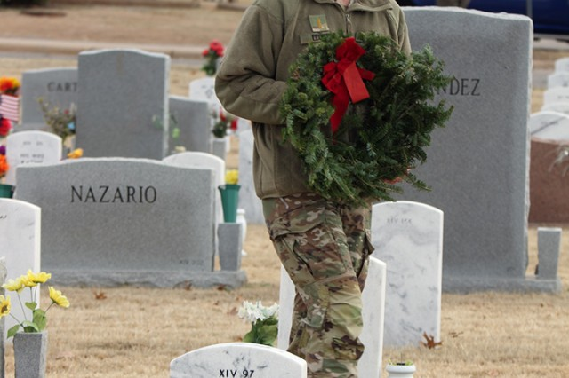 A Soldier prepares to lay a wreath at a grave site Dec. 14, 2019, at the post cemetery at Fort Sill, Oklahoma. Hundreds of people place over 1,000 wreaths. The wreaths are not Christmas wreaths for the holidays, but veterans wreaths, explained the event coordinator.