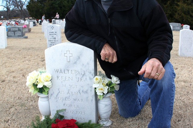 Retired Master Sgt. Ben Burris, of Lawton, Oklahoma, kneels by the headstone of his friend retired Master Sgt. Walter Keen Jr. Dec. 14, 2019, at the Fort Sill Post Cemetery. Burris attended the event with his friend Capt. Cullen O'Neill, who is a student in the Field Artillery Captains Career Course.