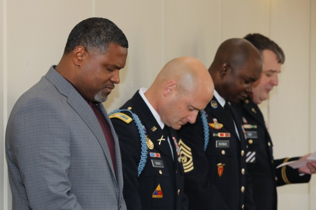 COLUMBUS, Ga. -- From left, Alonzo Stewart, Fort Benning Survivor Outreach Services; Col. Matthew Scalia, Fort Benning garrison commander; and Fort Benning Command Sgt. Maj. Connie Rounds bow their heads as Maj. Timothy Fary, the Fort Benning Family life chaplain, delivers an invocation before lunch. The Fort Benning Survivor Outreach Services hosted its annual holiday party at the RiverCenter for the Performing Arts Dec. 7 here. (U.S. Army photo by Markeith Horace, Maneuver Center of Excellence, Fort Benning Public Affairs)