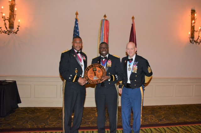 Maj. Gen. Patrick D. Sargent (left) and Cmd. Sgt. Maj. Buck O'Neal (right) present Lt. Gen. R. Scott Dingle (center) with a token of appreciation for providing guest speaker remarks during the 2019 MEDCoE Holiday Ball.