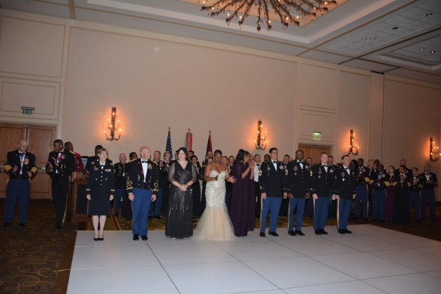 Awardees come forward to be inducted into the Order of Military Medical Merit during the 2019 MEDCoE Holiday Ball as prior inductees look on.  (Awardees Pictured left to right:  LTC Lisa A Lewis, LTC Paul Lang, LTC Kathleen Samsey, MSG April Hansberry, MSG Richard Jarrett, MSG Mark Dearlove, 1SG Cinnamon Chambers, 1SG Kyle Specht, and Drill Sergeant David Nagel).