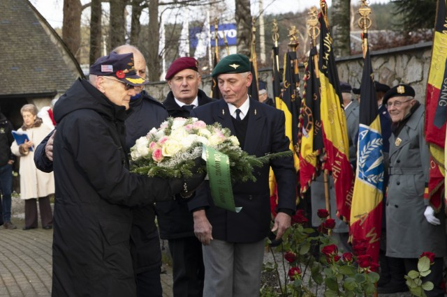 An American veteran presents a bouquet at the foot of the Malmedy Massacre Memorial in Malmedy, Belgium, in a ceremony on Dec. 15, 209, for the 75th anniversary of the massacre. The ceremony was held in remembrance of the victims of the war crime that resulted in the death of American prisoners of war. DoD photo by Sgt. Erica Earl / Released