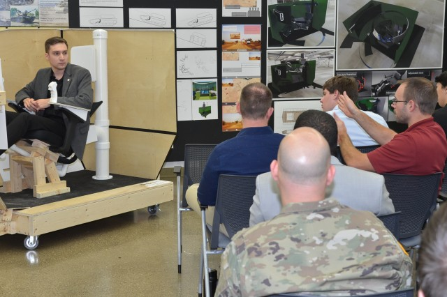 College for Creative Studies transportation design student Andrew Beauchamp, seated in the model he built of his interior design concept for future combat vehicles, responds to questions from engineers from the U.S. Army Ground Vehicle Systems Center. (U.S. Army photo by Jerome Aliotta/released)