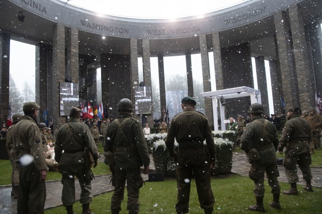 World War II reenactors and a simulated snow shower are part of the ceremony for the 75th anniversary of the Battle of the Bulge, at the Mardasson Memorial, Bastogne, Belgium, Dec. 16, 2019.
