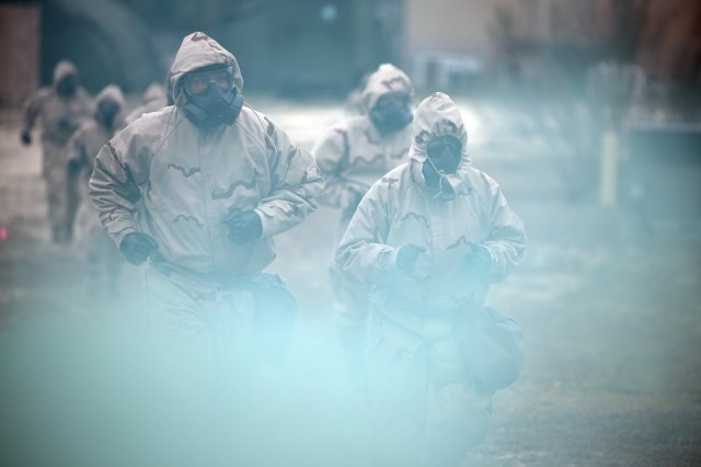 Soldiers wearing MOPP protective gear react to a simulated Chemical, Biological, Radiological, and Nuclear (CBRN) attack at Camp Bullis, TX.