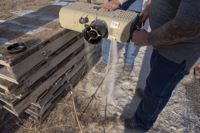 Technicians pour sand out of the SOM unit after the sand blowing test.