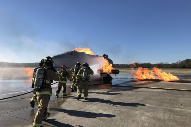 FORT BENNING, Ga. -- Fort Benning firefighters approach an aircraft fire simulator on foot. Firefighters with the Directorate of Emergency Services at Fort Benning and the Columbus Airport (CSG) conducted joint training on post at the Lawson Army Airfield Dec. 18. (U.S. Army photo by Bryan Gatchell, Maneuver Center of Excellence, Fort Benning Public Affairs)