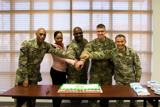 Members of the Eighth Army Chaplains Directorate prepare to cut a cake during a unit function that focused on the 110 years of the religious affairs specialist career field in the U.S. Army at U.S. Army Garrison-Humphreys, South Korea, Dec. 19. (U.S. Army photo by Cpl. Moon, Ji-hwan)