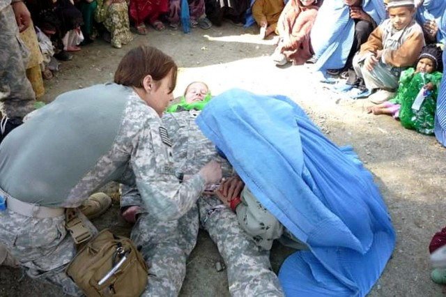 In a 2009 photo, then Sgt. Teresa Prupis conducts improvised tourniquet training to the local female populace in Afghanistan.