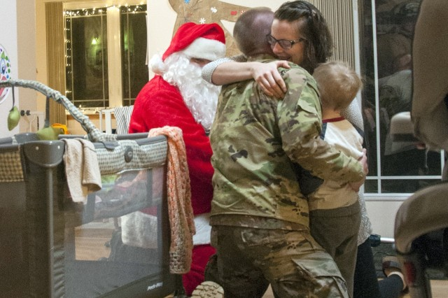 Capt. Jeff Grace, hugs his wife, Sara, and son, Remington, after surprising them by returning home early from his overseas deployment with the help of Santa Claus and the Fort Wainwright Fire Department on Dec. 18. Grace deployed earlier this year with the 1st Stryker Brigade Combat Team, 25th Infantry Division, in support of Operation Inherent Resolve. (Photo by Daniel Nelson, U.S. Army Garrison Alaska, Fort Wainwright Public Affairs)