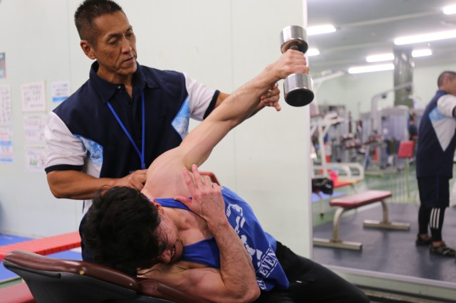 Kaoru Hashiguchi, an accounting technician with the 78th Signal Battalion at Camp Zama, Japan, helps Yukio Kondo, an administrative specialist with the 836th Transportation Battalion, with a weightlifting exercise Sept. 3 at the Sagamihara Gion Arena in Sagamihara City, Japan, where Hashiguchi works part time. Hashiguchi, 56, began training eight years ago to be a competitive bodybuilder and won his first championship in 2015.