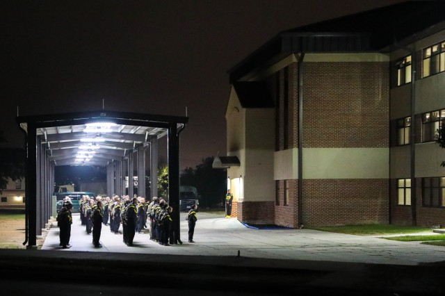 Basic Combat Training recruits at Fort Jackson, South Carolina stand in formation before dawn and await the day's tasks.