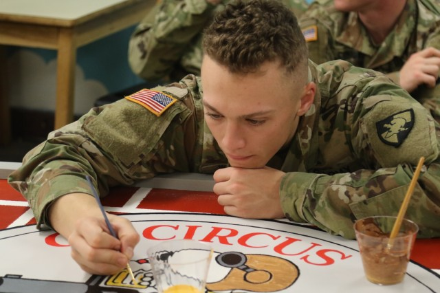 A cadet participates in the recreation of one of the seven murals C2 will take with them to their new home.