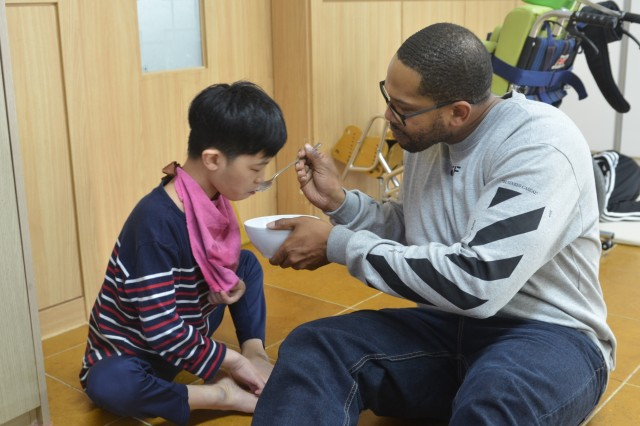 PYEONTAK, Republic of Korea--Sgt. First Class Maurice Jones, a GEOINT NCOIC with Headquarters and Headquarters Troop, 3rd Armored Brigade Combat Team, 1st Cavalry Division feeds a resident of a special needs orphanage here. Soldiers from the Greywolf Brigade have been volunteering throughout their nine-month rotation to build relationships and give back to the Korean people.