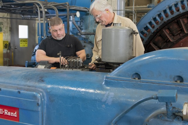 Shane Nobles, left, and Glean Heath adjust the lubrication for a compressor in the Condensed Air Shop at Anniston Army Depot.