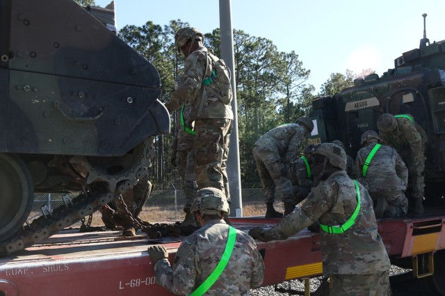 Soldiers with the 1st Armored Brigade Combat Team chain down armored vehicles to a railcar Dec. 18, 2019 at the Rail Marshalling Area, Fort Stewart, Georgia.  The vehicles will be transported to the National Training Center, Fort Irwin, California for 1ABCT's upcoming training rotation. (U.S. Army photo by Spc. William Griffen)