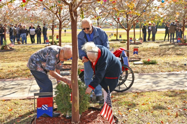 """Sergeant Maj. (Ret.) Robert Halderman, his wife Betty, and her son Paul Lowe, of Savannah, place a wreath at the base of the tree dedicated to Staff Sgt. Vincent Summers, Dec. 14, 2019, at Fort Stewart's Warrior Walk bordering Cottrell Field. Fort Stewart hosted Wreaths for Warriors Walk, in conjunction with the national """"Wreaths across America"""", to honor and show support to the families of the fallen Soldiers of Fort Stewart and Hunter Army Airfield. (Photo by Staff Sgt. Todd Pouliot, 50th Public Affairs Detachment)"""