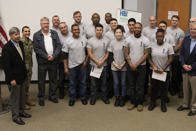 Graduates gather for a photo during a Home Builder Institute Transitioning Military Program graduation ceremony at the Education Center on Fort Stewart, Ga., Dec. 13, 2019. HBI prepares transitioning Soldiers to attend training and receive job skills that will qualify the Soldiers to fill positions available in the construction industry. (U.S. Army photo by Sgt. Zoe Garbarino)