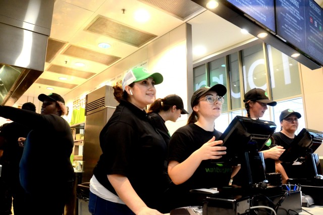 Kendra Jackson, green and white hat, greets customers during the lunch rush at Wahlburgers in the Kaiserslautern Military Community Center on Ramstein Air Base. Jackson, a military spouse of 11 years with three small children, was hired as general manager of the new restaurant in November. Wahlburgers opened Jan 8.